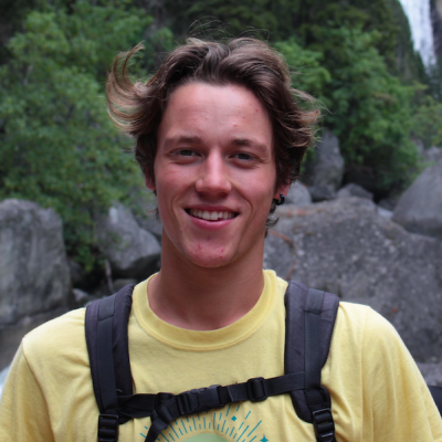 A picture of Keir smiling, outdoors in nature, wearing a yellow t-shirt and a backpack